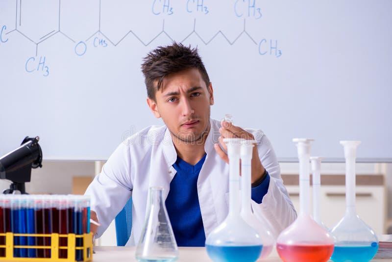 Il giovane chimico che si siede in laboratorio fotografia stock