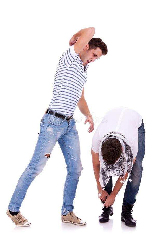Il giovane colpisce il suo amico con il suo gomito fotografia stock libera da diritti