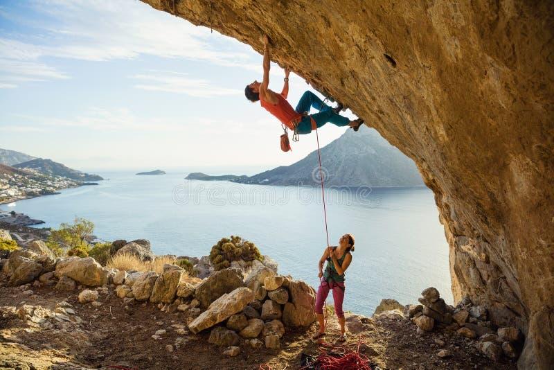 Il giovane comincia scalare in caverna, il suo atto del legare femminile del partner lui fotografie stock