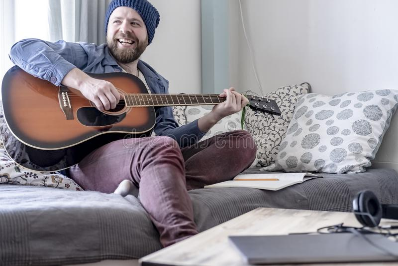 Il giovane compositore gioca la musica scritta sulla chitarra acustica, piacevole con il risultato, sorridente felicemente ai suo fotografia stock libera da diritti