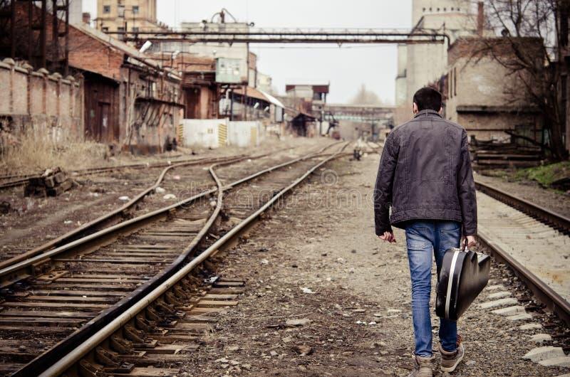Il giovane con la cassa della chitarra sta andando via fotografia stock libera da diritti