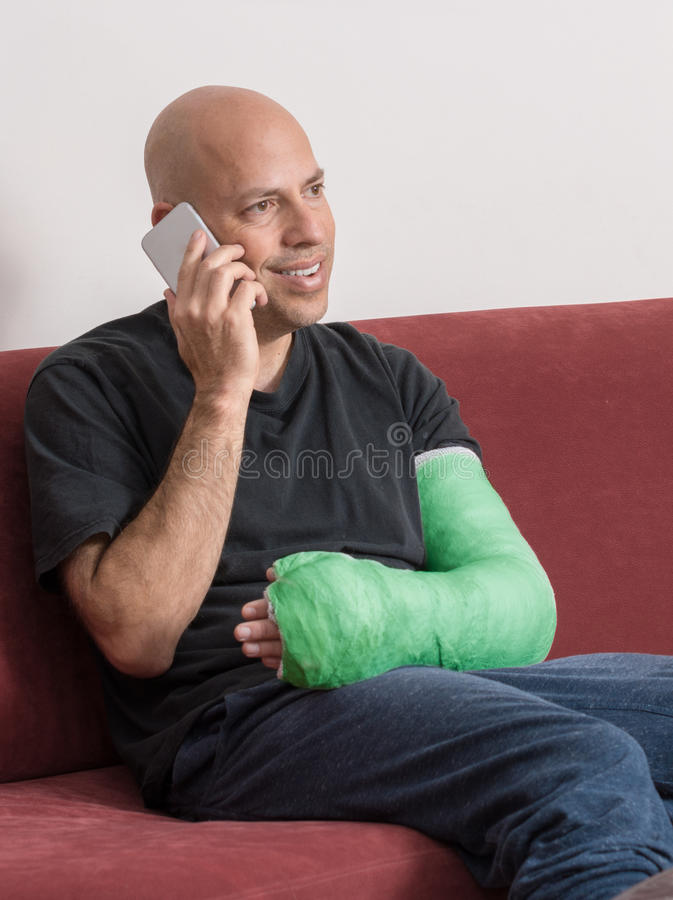 Il giovane con un braccio ha fuso la conversazione sul suo telefono fotografia stock libera da diritti