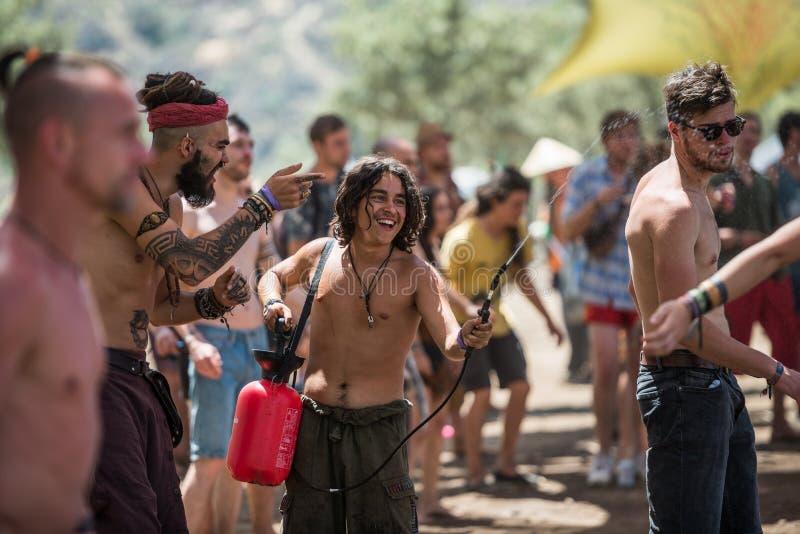 Il giovane con un diffusore dell'acqua rinfresca il pubblico sulla fase principale del festival di musica perso dello psytransce  immagini stock