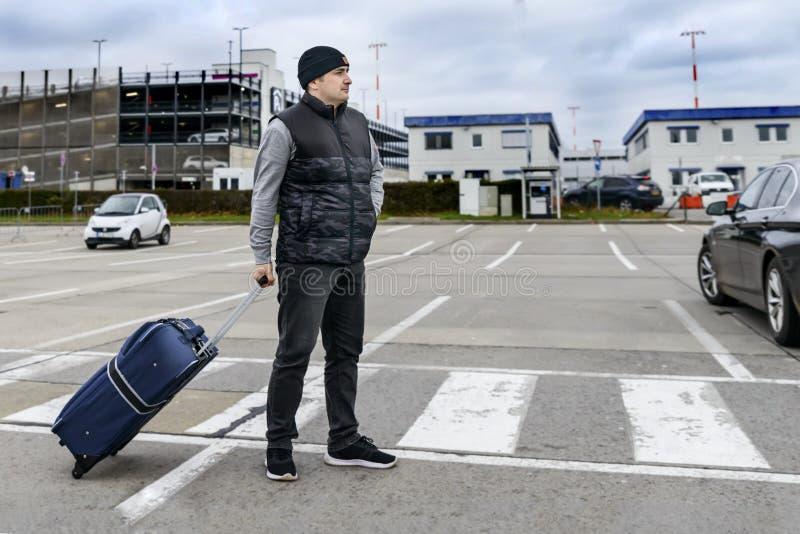 Il giovane con una valigia sta sulla strada davanti alla costruzione dell'aeroporto: fotografia stock libera da diritti