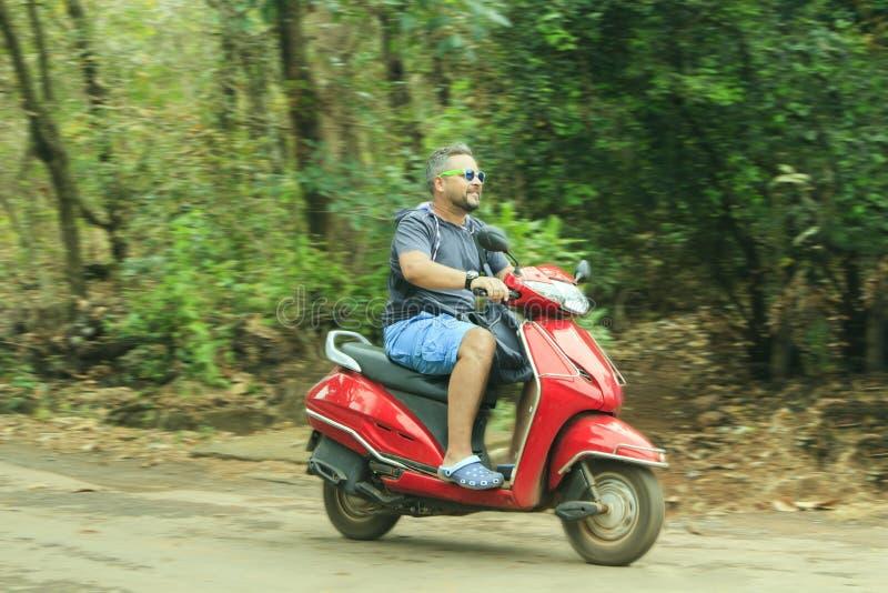 Il giovane conduce un motociclo rosso fotografie stock