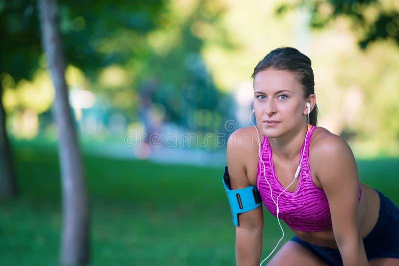 Il giovane corridore femminile sta avendo rottura e sta ascoltando musica durante il funzionamento in città su una banchina fotografie stock