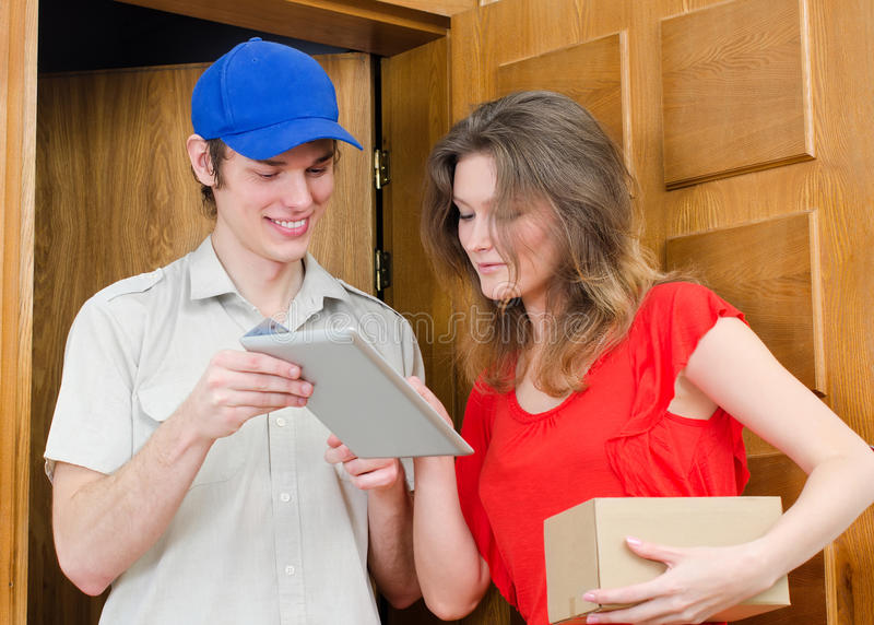 Il giovane corriere consegna il pacchetto fotografia stock