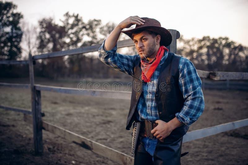 Il giovane cowboy posa contro il recinto per bestiame del cavallo immagine stock libera da diritti