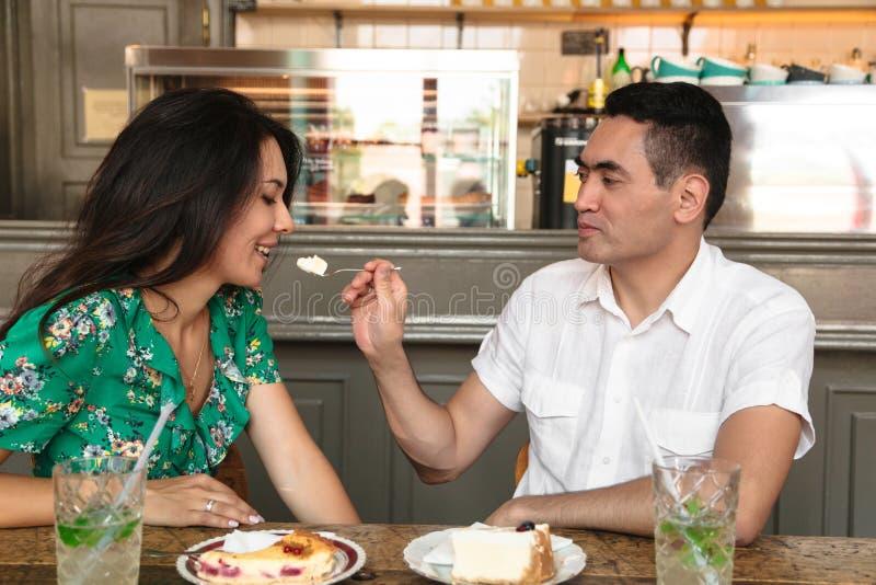 Il giovane dà un pezzo di dolce alla sua moglie immagini stock
