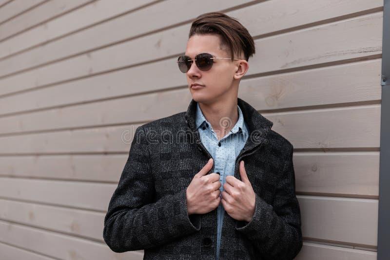 Il giovane dei pantaloni a vita bassa europei in un rivestimento d'avanguardia del plaid in una camicia d'annata in occhiali da s fotografia stock libera da diritti