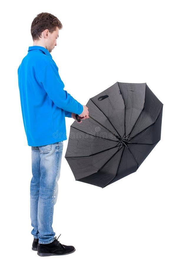Il giovane dentro in un bianco tricotta il maglione sotto un ombrello immagini stock libere da diritti