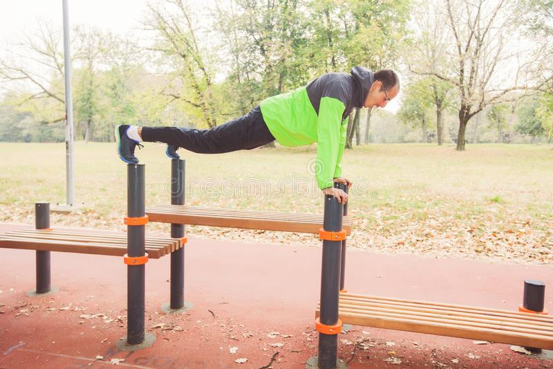 Il giovane di forma fisica che fa Spinta-UPS agli sport all'aperto parcheggia fotografia stock libera da diritti