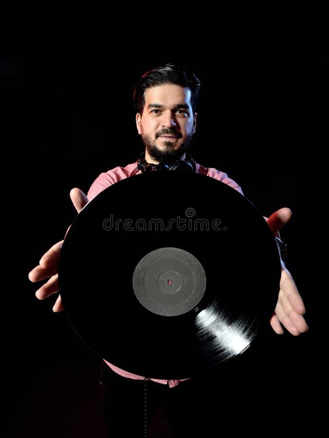 Il giovane DJ nell'annotazione di vinile bianca della tenuta del costume dentro fotografia stock