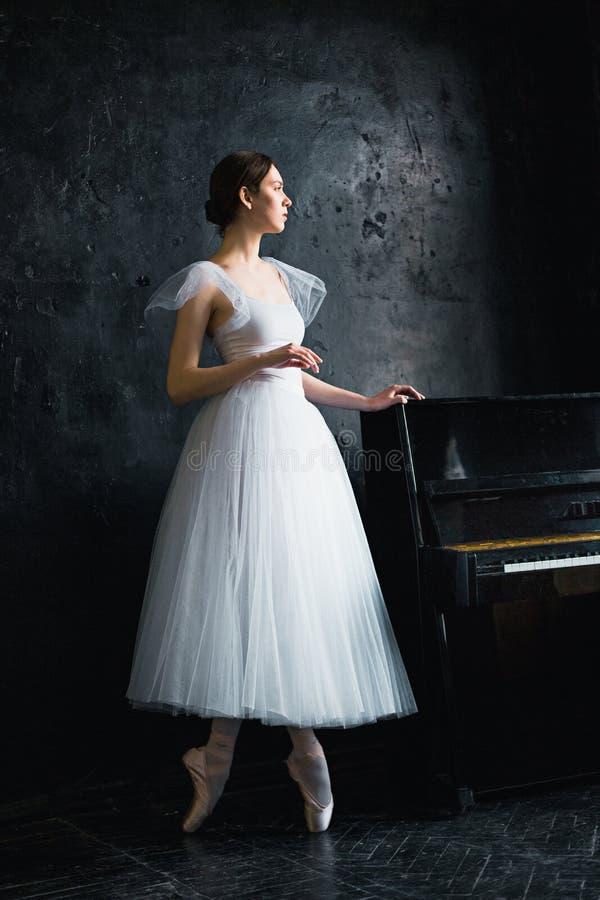 Il giovane e la ballerina incredibilmente bella sta posando in uno studio nero fotografie stock libere da diritti