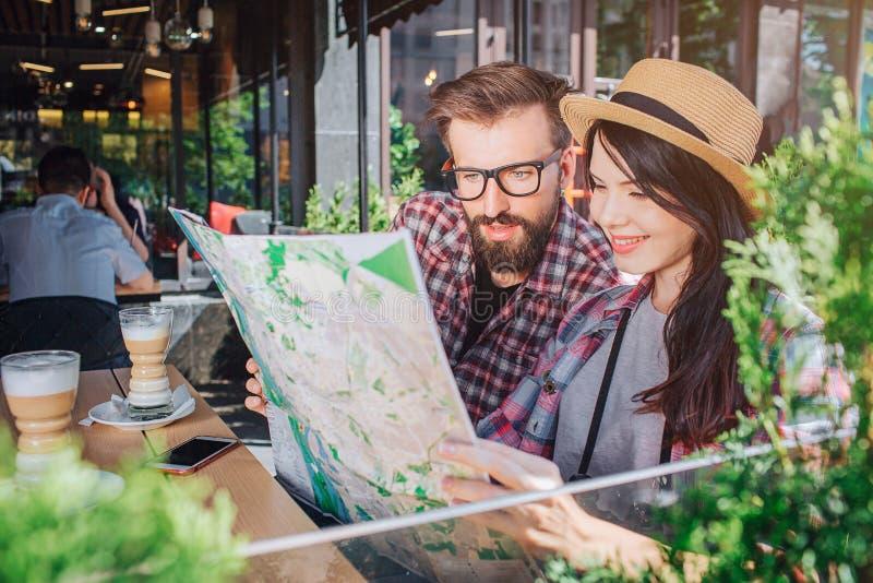 Il giovane e la donna di Interester si siedono ed esaminano la mappa che tiene Sorrisi della donna Il tipo è serio Hanno resto là immagini stock libere da diritti