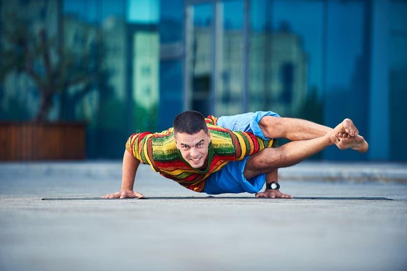 Il giovane fa pratica con handstand yoga asana Ashtavakrasana posano all'aperto sullo sfondo di una città moderna immagini stock