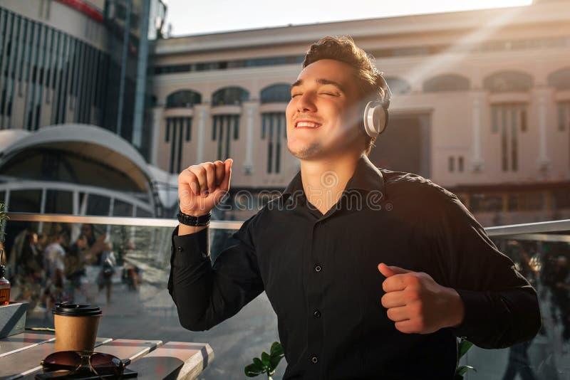 Il giovane felice gode di di ascoltare la musica Balla alla tavola fuori Onda del tipo con le mani È esterno soleggiato immagine stock