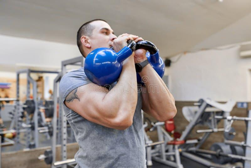 Il giovane forte culturista muscolare dell'atleta solleva i pesi nella palestra, addestramento del peso fotografia stock