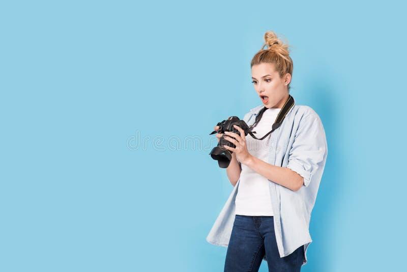 Il giovane fotografo biondo è colpito circa la foto che ha fatto fotografie stock libere da diritti