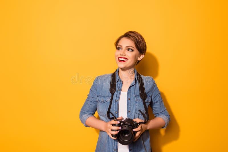 Il giovane fotografo femminile alla moda sta sorridendo sulla b gialla fotografie stock