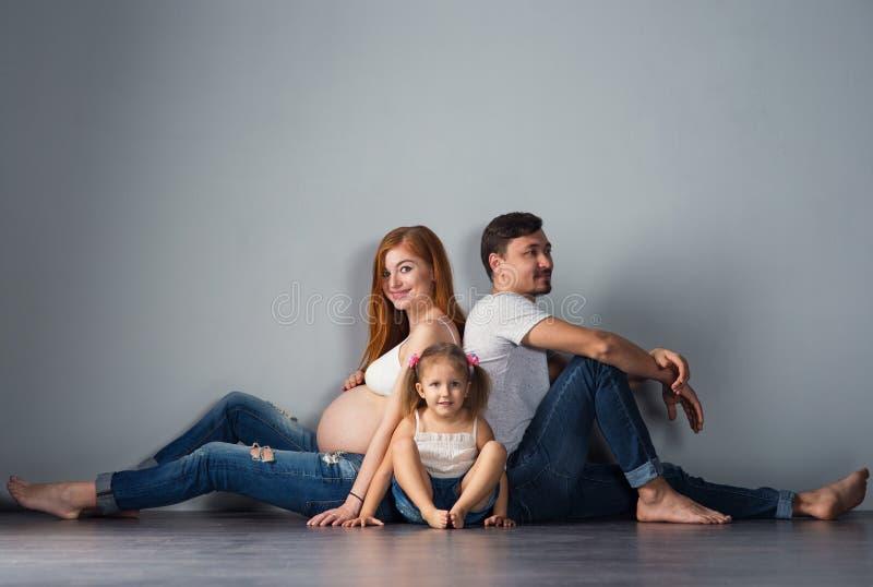 Il giovane futuro parents un uomo e una donna incinta dai capelli rossi con fotografia stock