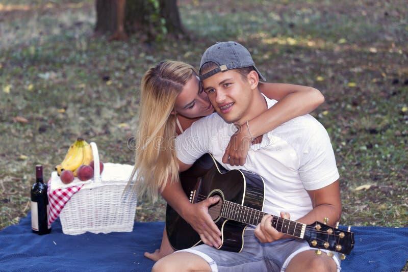 Il giovane gioca la chitarra, mentre la ragazza che gode della musica immagini stock libere da diritti