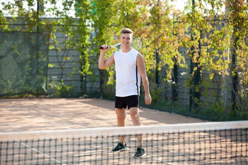 Il giovane gioca a tennis all'aperto sulla corte arancio immagini stock libere da diritti