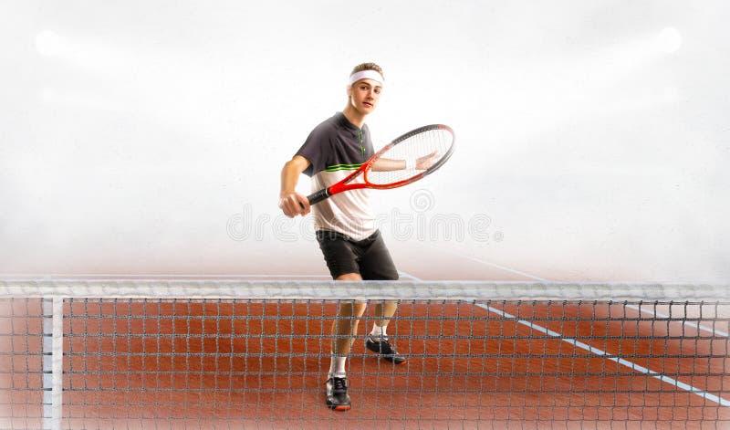 Il giovane gioca a tennis alla corte immagini stock