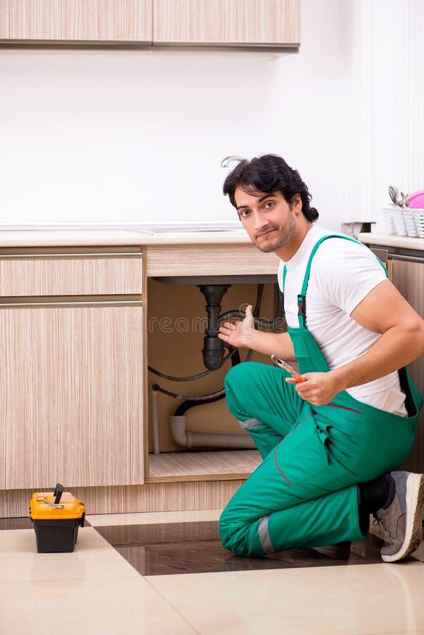Il giovane idraulico che ripara il lavabo alla cucina immagini stock libere da diritti