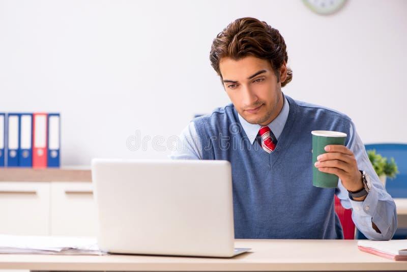 Il giovane impiegato bello che lavora nell'ufficio fotografie stock