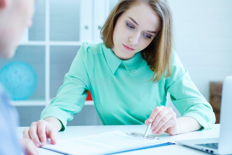 Il giovane impiegato femminile dell'agenzia di assunzione di personale contribuisce a compilare la forma al cercatore di lavoro m fotografie stock