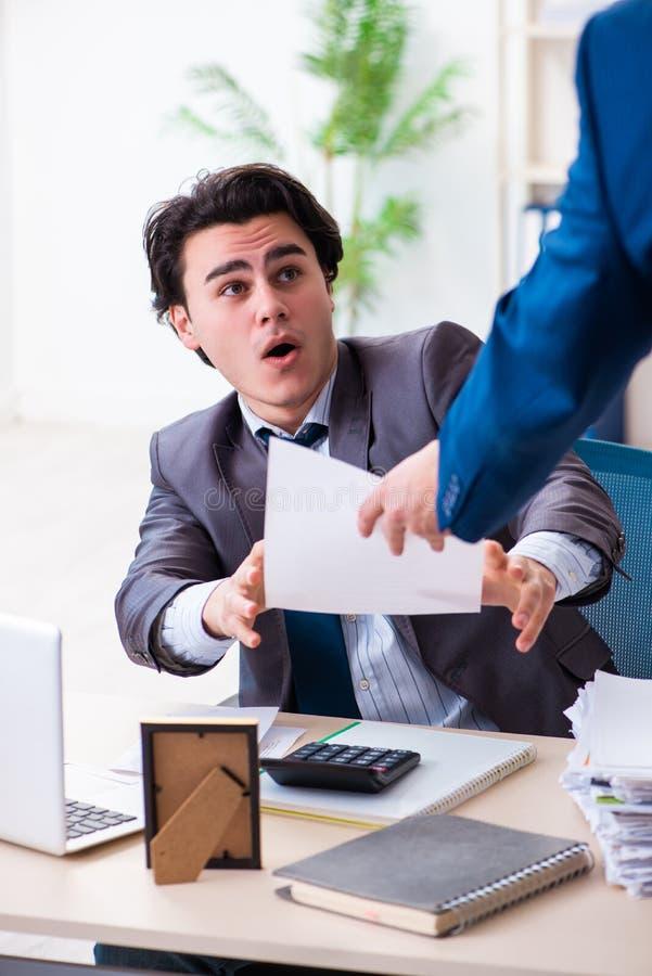 Il giovane impiegato maschio che ? infornato dal suo lavoro immagini stock libere da diritti