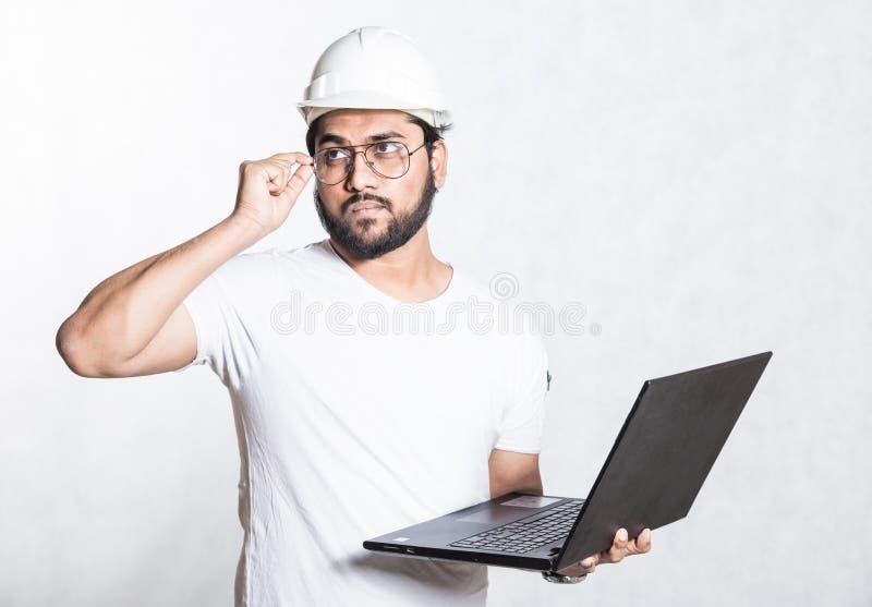Il giovane ingegnere del costruttore in vetri ed in un casco di sicurezza bianco, sta con un computer portatile aperto immagine stock libera da diritti