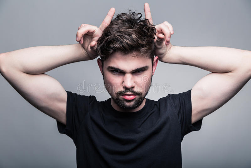 Il giovane in maglietta nera mostra il corno immagine stock libera da diritti
