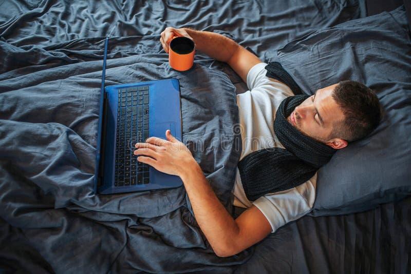 Il giovane malato lavora a casa Esamina lo schermo del computer portatile e della mano della tenuta sulla tastiera Il tipo tiene  immagine stock libera da diritti