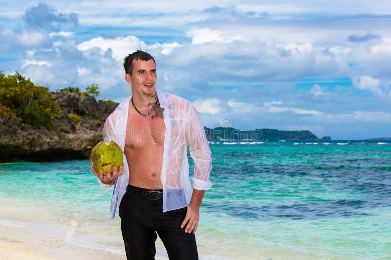 Il giovane maschio bello felice che dura in camicia bianca sta stando sopra fotografia stock