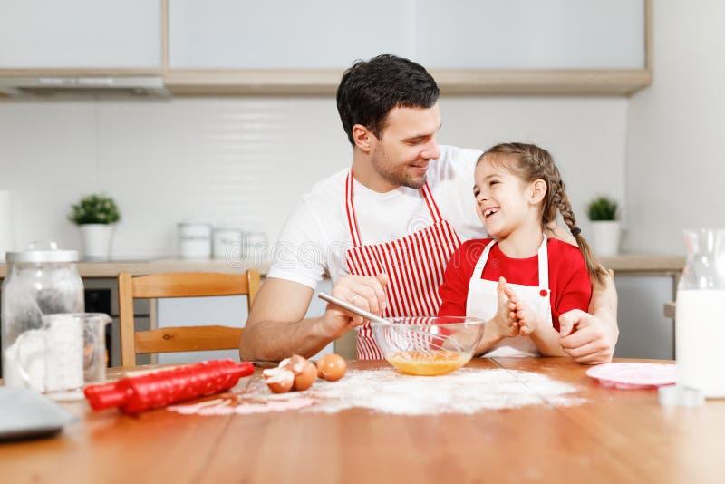 Il giovane maschio della brunetta affettuosa abbraccia la figlia, si siede insieme alla cucina, cuoce qualche cosa di delizioso,  immagini stock libere da diritti
