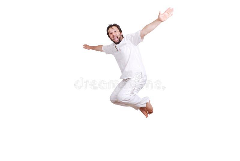 Il giovane maschio felice in vestiti bianchi sta saltando fotografia stock libera da diritti