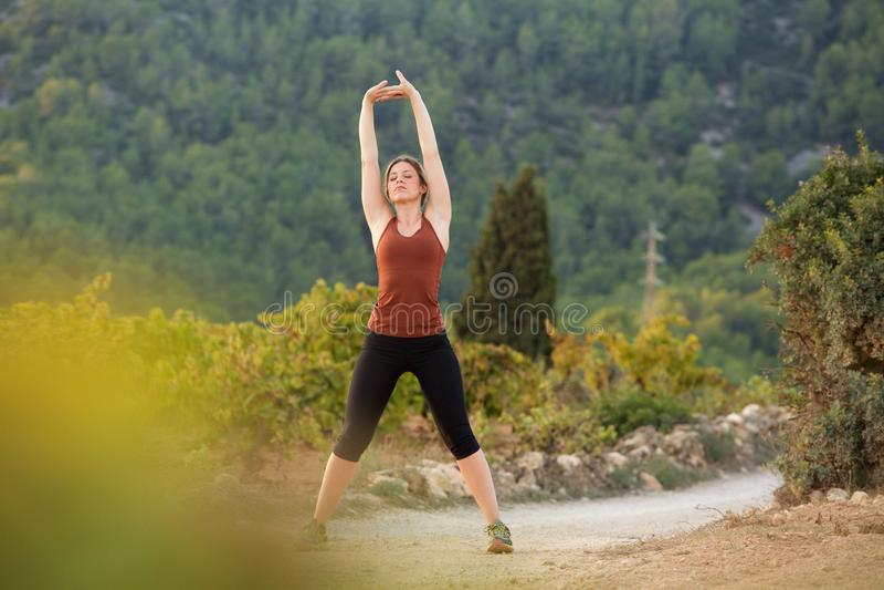 Il giovane mette in mostra la donna che allunga l'esercizio con le armi alzate fotografie stock libere da diritti