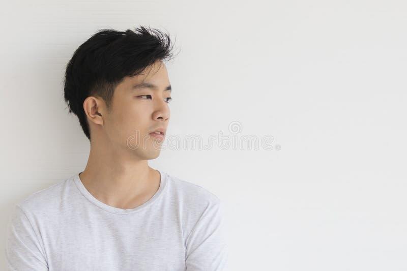 Il giovane modello asiatico dell'uomo in maglietta ha attraversato il braccio immagini stock libere da diritti
