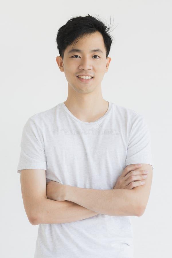 Il giovane modello asiatico dell'uomo in maglietta ha attraversato il braccio immagine stock libera da diritti