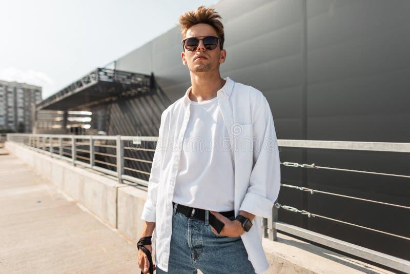 Il giovane modello di moda bello americano dell'uomo in camicia alla moda bianca in jeans d'annata blu in occhiali da sole d'avan fotografie stock libere da diritti
