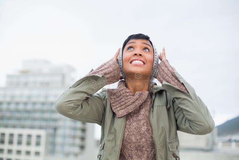 Il giovane modello disturbato nell'inverno copre l'ostruzione delle sue orecchie fotografia stock libera da diritti