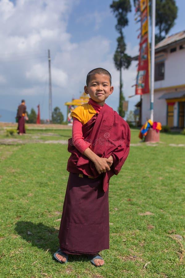 Il giovane monaco buddista non identificato del principiante nel rosso tradizionale veste la condizione davanti ad un monastero i fotografia stock libera da diritti