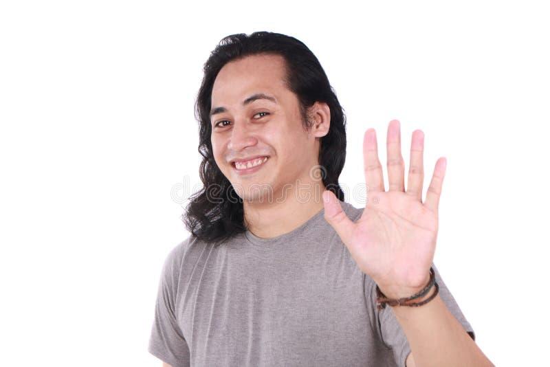 Il giovane mostra ciao o alto gesto cinque immagini stock