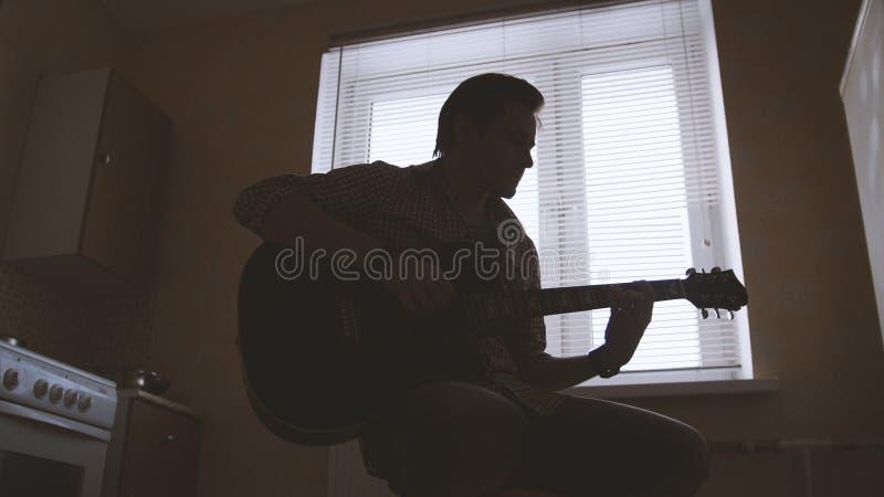 Il giovane musicista attraente compone la musica sulla chitarra ed i giochi, l'altro strumento musicale nella priorità alta, silu immagini stock libere da diritti
