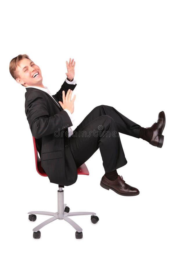 Il giovane nella risata del vestito si siede sulla presidenza fotografia stock libera da diritti