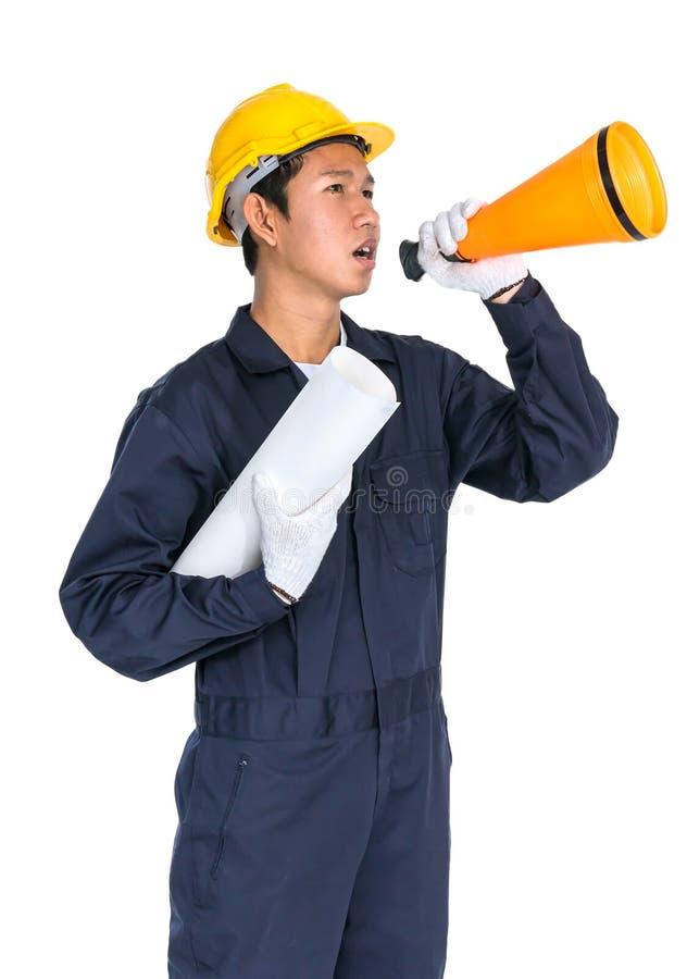 Il giovane operaio che grida per annuncia tramite un megafono immagini stock