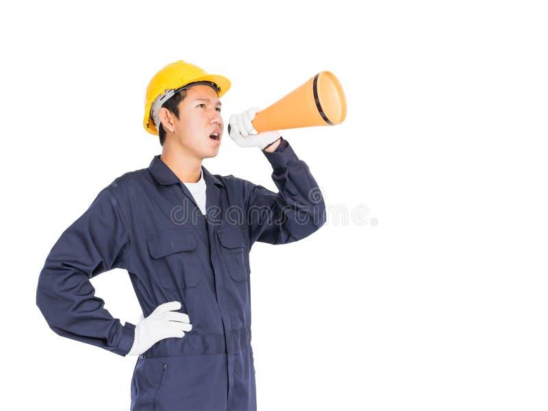 Il giovane operaio che grida per annuncia tramite un megafono immagine stock