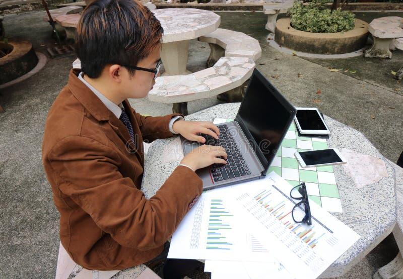 Il giovane operaio sta utilizzando il computer portatile con lo schermo in bianco, il lavoro di ufficio ed il telefono cellulare  fotografie stock libere da diritti